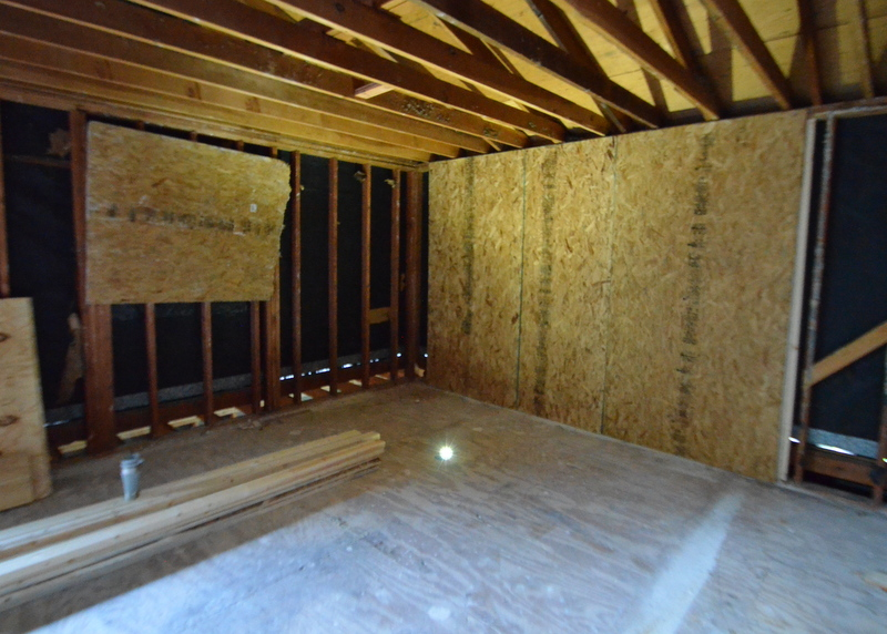 From inside what will be the master bedroom, OSB sheathing closes off what will be the new front windows, with the original side window also closed off. The bright light on the floor is Steven's cell phone, providing enough light for the camera autofocus to shoot.