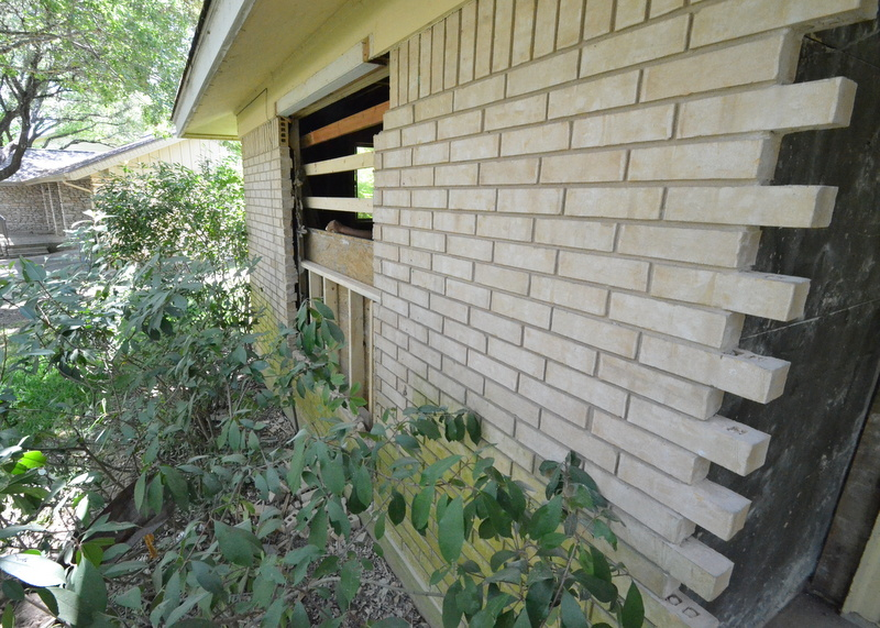 Also outside, at the front left of house, brick is removed to enlarge the front window of bedroom 1.