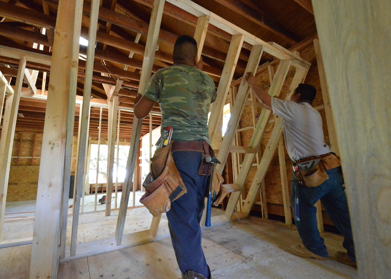 The framers raise the interior wall between what will be bath 3 and the utility/laundry room.
