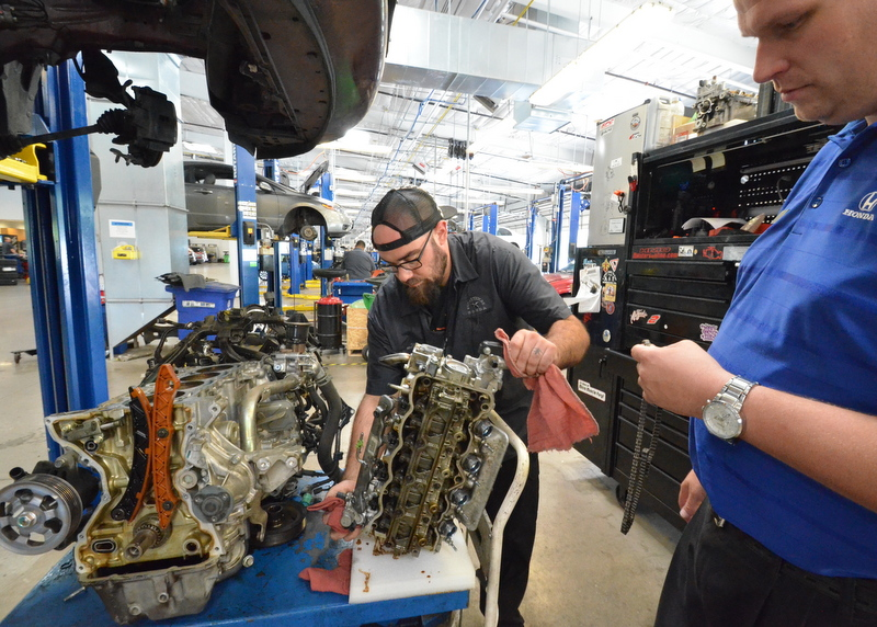 Chris, the service tech, turns over the upper half of the engine block for show and tell.