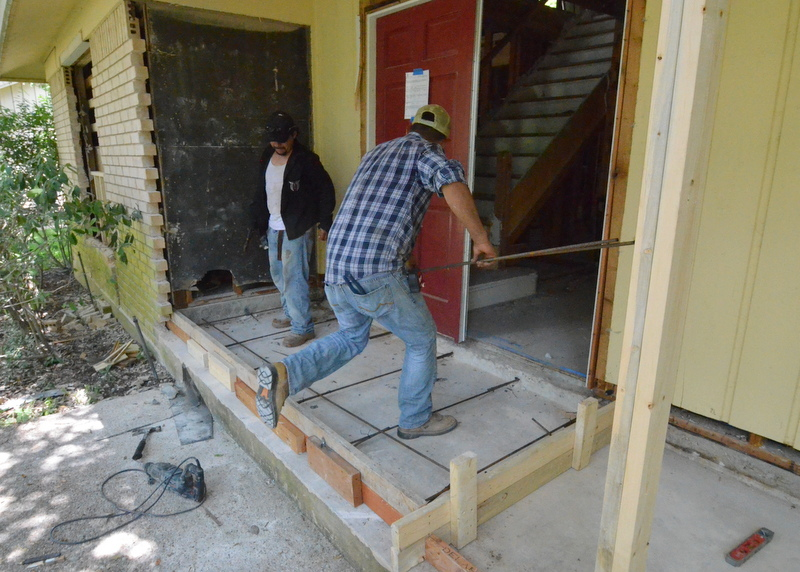 "At mid-day, the concrete team builds forms and drills rebar reinforcing rods into the existing slab as the prepare to pour the new concrete needed to bring the slab up 2+ inches to level the floor where we are extending the front entry forward -- all because the stairs are not to code and we need additional ""run"" length for the math and material to work correctly."