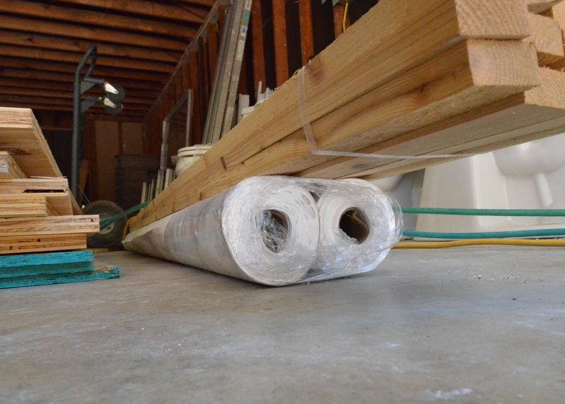 Two rolls of Tyvek house wrap and trim lumber, stored on the garage floor.