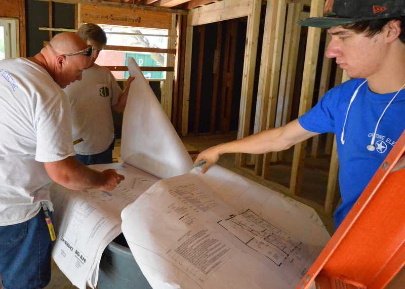 Sean, left, and Ron, at back, debate where to put the ceiling cans if the kitchen has 10 extra inches now that the framing is up -- the room is 10 inches wider than calculated in the plans. Jacquela will enjoy the extra space in the kitchen.