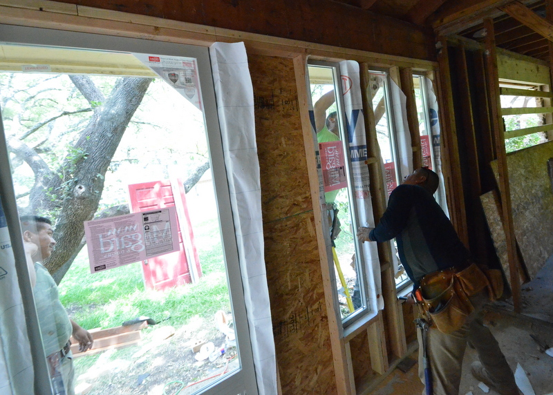 Here the framers test fit the three narrow windows at the redesigned front entry.