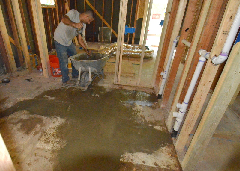 Cris from Ranserve mixes concrete to patch the floor of bath 2 where the plumbers jackhammered to run new pipes.