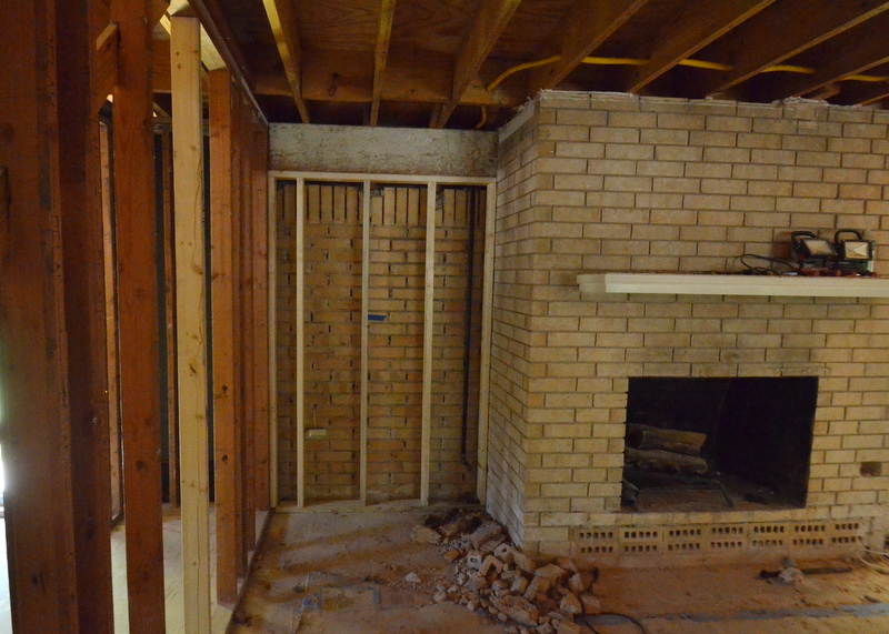 To the left of the fireplace, a new short wall is framed into place, replacing a brick wall and an extension of the brick hearth that were removed several days back by the demo team.
