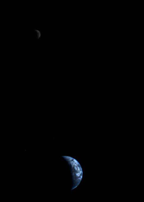 This picture of the Earth and moon in a single frame -- the first of its kind ever taken by a spacecraft -- was recorded 18 September 1977, by NASA's Voyager 1 when it was 11.66 million km (7.25 million miles) from Earth. The moon is at the top of the picture and beyond the Earth as viewed by Voyager. In the picture are eastern Asia, the western Pacific Ocean and part of the Arctic. Voyager 1 was directly above Mt. Everest (on the night side of the planet at 25 degrees north latitude) when this picture was taken. The photo was made from three images taken through color filters, then processed by the Image Processing Lab at the Jet Propulsion Laboratory (JPL). Because the Earth is many times brighter than the moon, the moon was artificially brightened by a factor of three relative to the Earth by computer enhancement so that both bodies would show clearly in the image. Credit: NASA