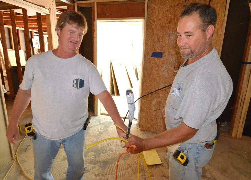 "Ron, left, and Steve, right, show four of the different types of electrical wire that Capstone is threading through studs, joists and rafters. Yellow to power the microwave and oven, black to power the induction cooktop, and two different yellow wires -- ""two pair"" and heavier gauge ""three pair."""