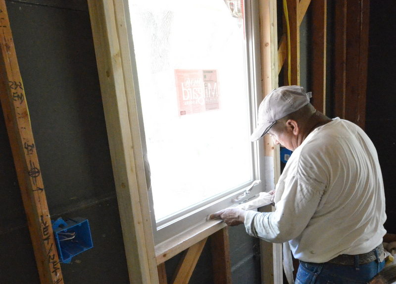 The painters are caulking the windows, sealing up the house with silicon in preparation for expanding foam insulation. Only the lower portion of each window is caulked. Ron explains that the top and sides will be sealed with foam.