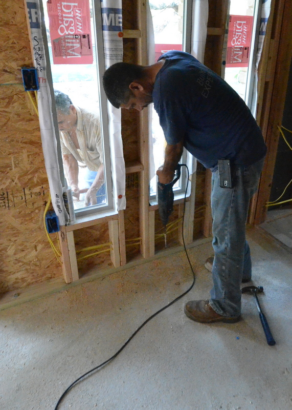 Cris from Ranserve uses a hammer drill on the floor plate at the new front wall of the new entry -- while Gabriel the mason works on the other side of the window, laying brick.