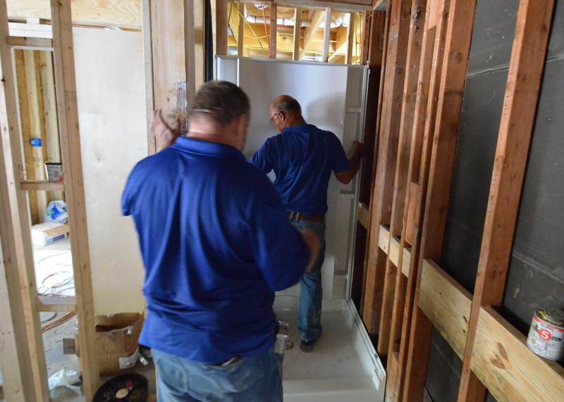 With the shower pan already cemented into place, Barry, at right, positions the rear shower wall while Albert  calls out flange locations.