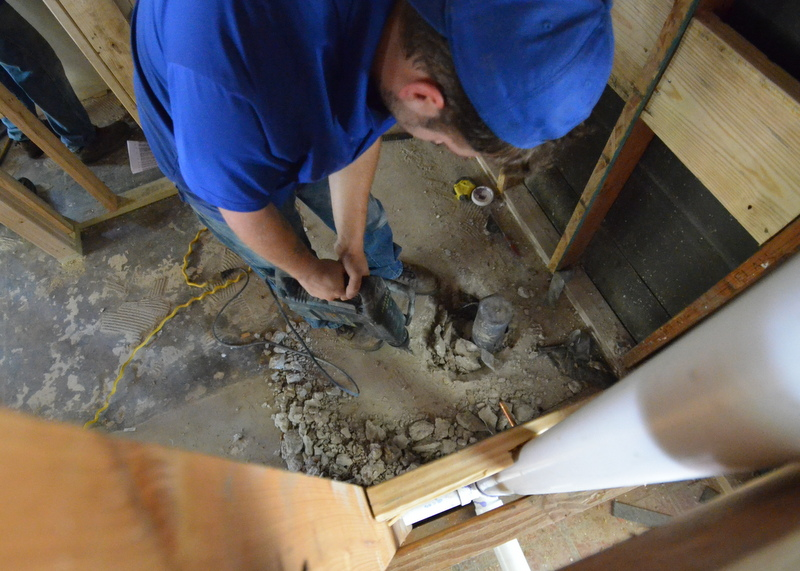 The plumbers are busting concrete around the toilet drain in the mudroom bath, in order to pivot the toilet 90 degrees -- a better design for the use of space in this small bath, realized only after it was framed and rough-plumbed.