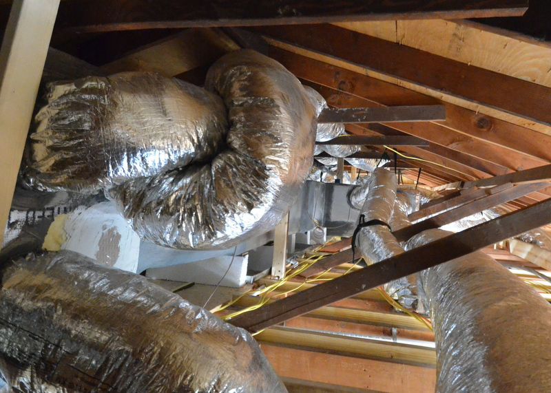 At left, two return ducts knot around each other. Why? Then the lower duct is pulled up to the peak of the attic, crammed into the narrow space created by the horizontal collar ties, and choked four times as it travels across four collar ties. Why? And, in this position, the insulation installers will never be able to blow foam against the roof to properly insulate the house. The solution is to untie the knot, extend the duct run to the right side of the attic in this photo, rest the duct against the ceiling rafters, let it travel out to the north side of the attic, relaxed, improving airflow and efficiency. Why didn't Elite think of and do this?