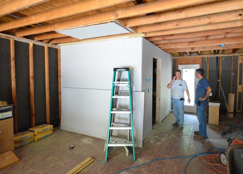 Ron, left, and Cris, right, in the garage, with drywall wrapping around the mudroom.