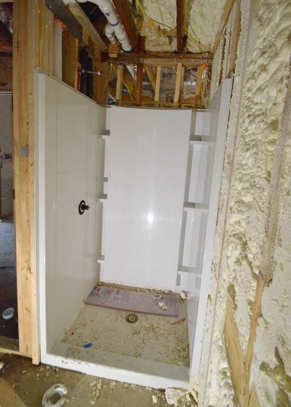 Next day, the left-side panel wall and shower valve fitting are both in place.