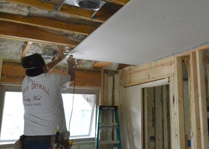 First sheet of drywall attached to kitchen ceiling; installer cuts out drywall for a ceiling can.