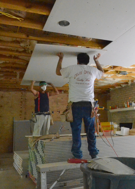 The crew from Celis Drywall uses their heads -- the time-honored technique for hoisting drywall over your head to the ceiling.