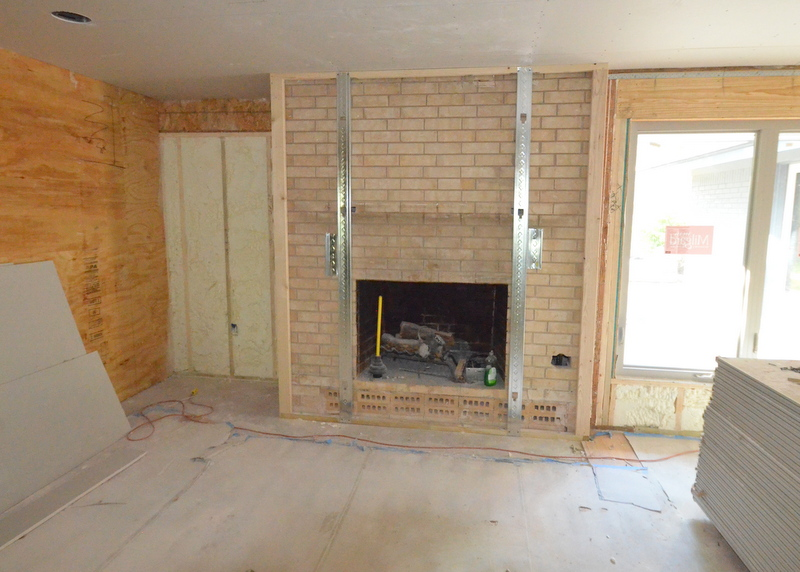 Ron Dahlke is using steel studs to frame the fireplace, prepping the brick to be covered by fire-resistant drywall. This is one of the design mandates for Emerald Hill -- get rid of the yellow brick, either by paint on the exterior or drywall on the interior.