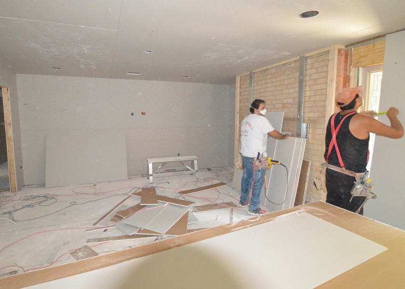 In the family room, Jose, left, and Andres, right, prep drywall for the south wall.