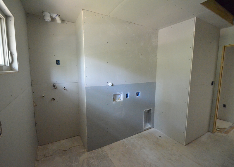 "All the upstairs rooms are complete. Here's the ""wet wall"" in the utility/laundry room. The darker drywall is water resistant. One of the tankless units will be mounted in the niche at left. The washer will be located near the center of the photo, with the dryer installed in front of the large dryer vent near the floor and corner at right center."