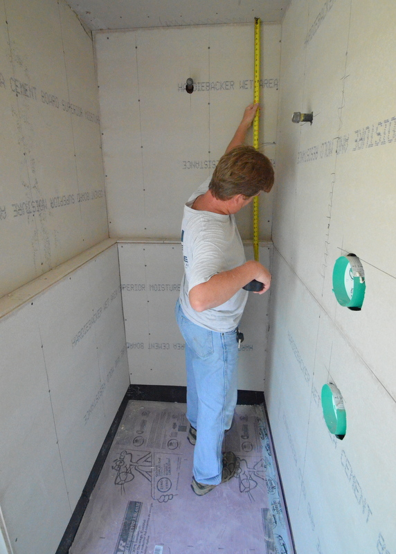 Steven thinks the right side of the shelf in the master shower is lower than the left corner -- and all water will drain into the right corner instead instead of the shower. Ron pulls out his tape measure and checks. Yup. 1/4 inch off.