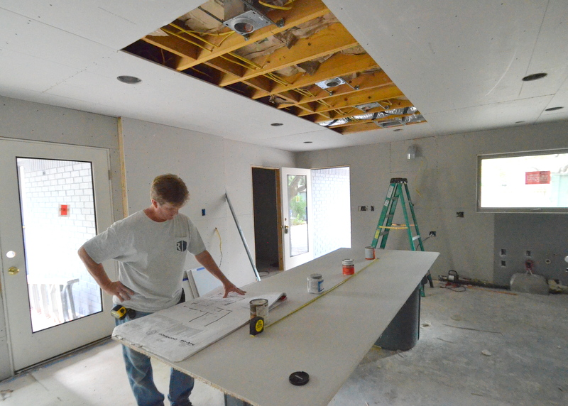 Here's Ron Dahlke studying the plans, with the drywall mockup of the kitchen island propped on two garbage cans and four paint cans approximating the location of the four recessed cans that will be used to illuminate the island.
