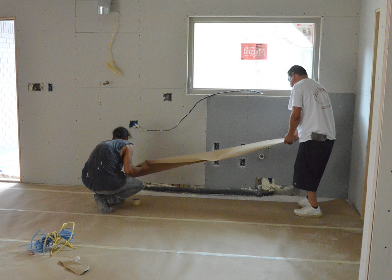 Anthony and Gelipe prepped the entire house with heavy-duty paper to protect the floors against the mudding mess that spackle will create ...