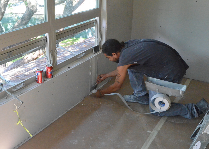 "Anthony applies tape to the ""mud"" to seal the joint between two pieces of drywall."