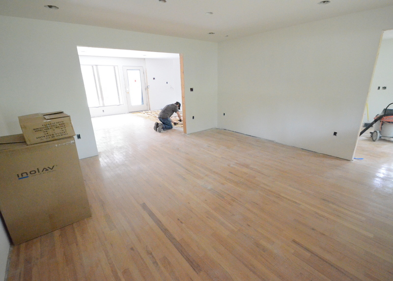 From the library at the front of the house, Kevin chisels up the oak flooring in the family room.