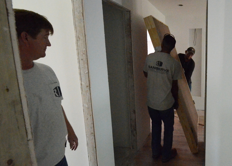 Ron supervises while Cris navigates a closet door through the hallway to bedroom 1.