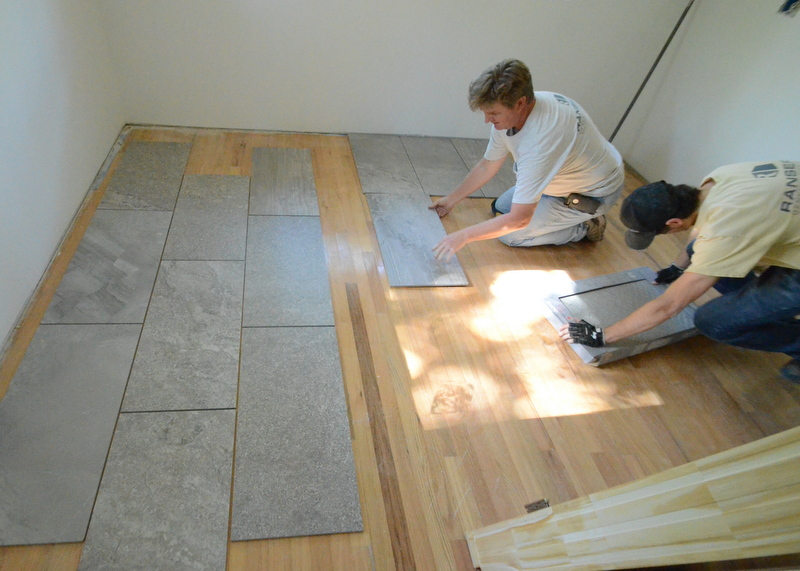 Ron laying out two potential patterns of the large tile for the kitchen, using the floor in Steven's office to see how the tile looks next to wood. Kevin delivers more tile. Brick pattern at left, with Ron laying out a basic grid. One observation as we see the tile exposed, out of the box, for the first time -- there are two basic designs printed by inkjet onto the porcelain -- a linear design, and a mottled or speckled look. It will be important to mix the two designs, or to segregate one from the other by allocating one design to a specific space, and the second design to a different space. This may be possible, as this tile will be used for the kitchen, mudroom and pantry, with doors between the three spaces.