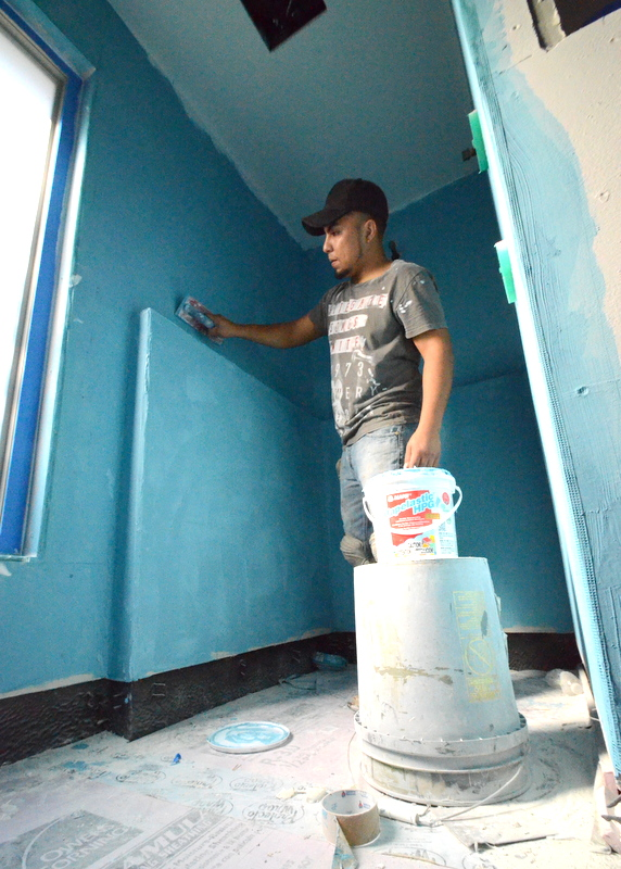 Upstairs in the master shower, Pedro applies a second layer of blue waterproofing to the Hardie board.