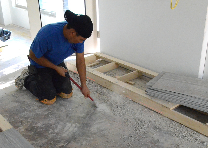 Manuel scrapes the last of the old cement off the slab floor -- cement left behind when demo removed the orange saltillo tiles from the kitchen floor that came with Emerald Hill.