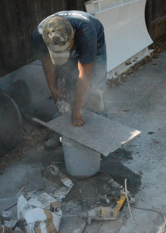 Outside on the driveway, Pedro raises a cloud of porcelain dust as he grinds a slot into a tile that wraps around a doorway.