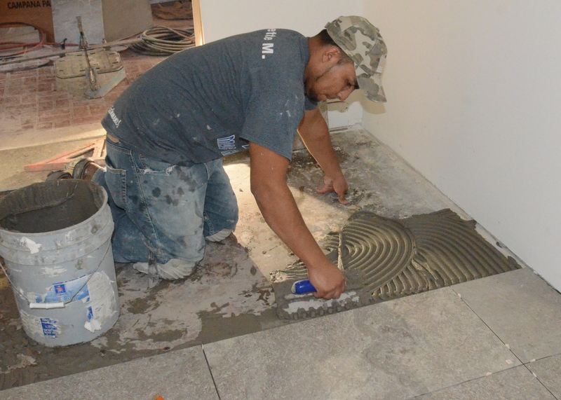 Pedro trowels cement onto the mudroom floor.