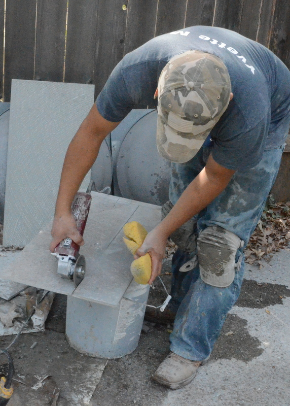 Back outside, Pedro freehands the cut into another floor tile.