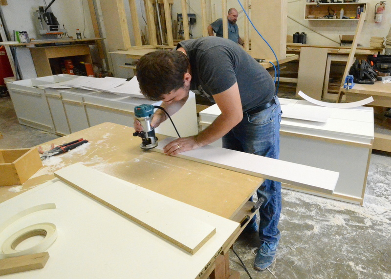 Bani uses a trim router to finish the edge of the white laminate piece that will be installed at the front of a cabinet.