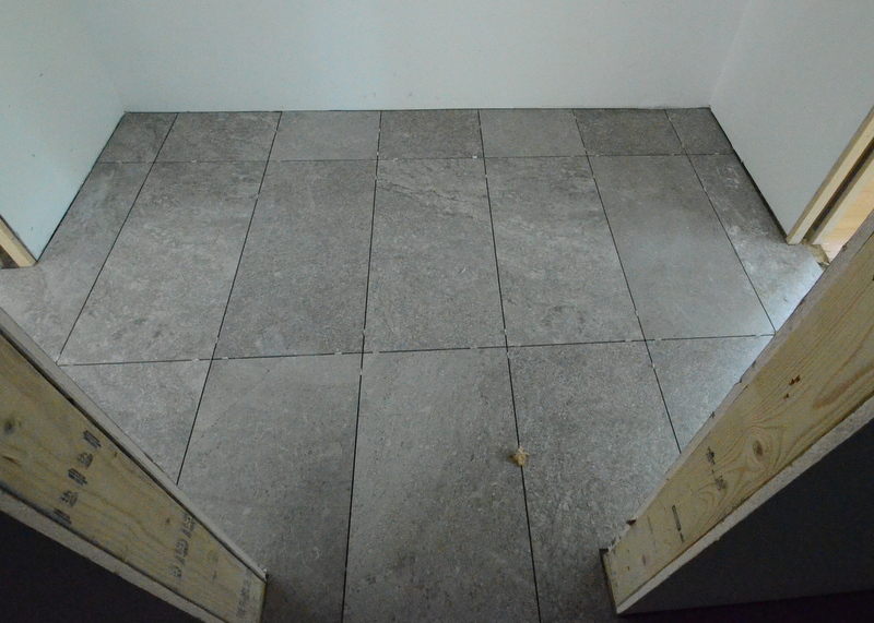 Part of the pantry hallway, shot from inside the pantry, looking out. The man-made porcelain tile resembles mottled granite.