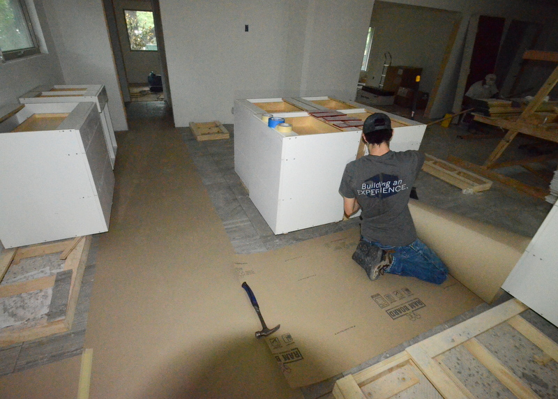 In the kitchen, Kevin works around the first cabinets delivered, protecting the tile floor with layers of heavy paper.