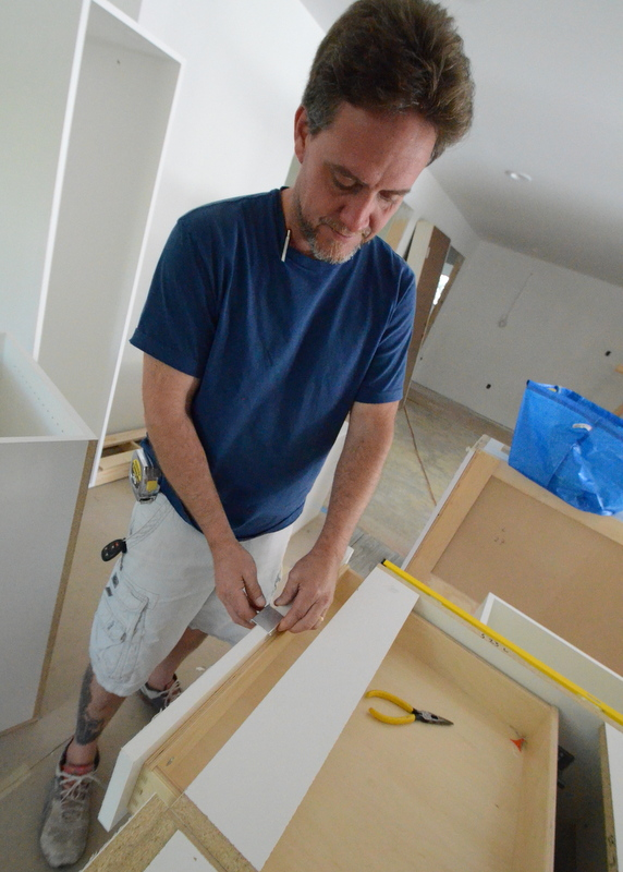 Aaron test fits one of the Ikea handles on a cabinet drawer. Yes, it fits and will do the job we ask of it. Minimal. Linear. Functional.