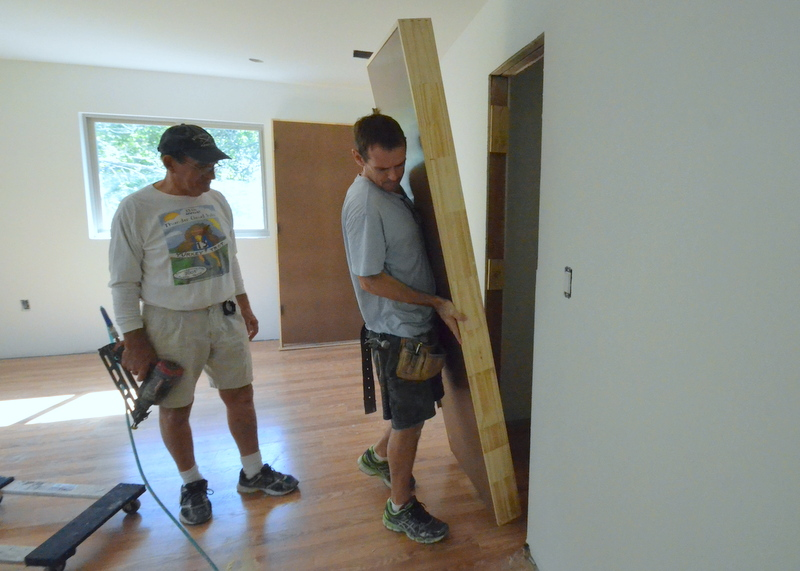 Patrick's got the nail gun ready as Shane hoists into place the closet door in what will be the train room.
