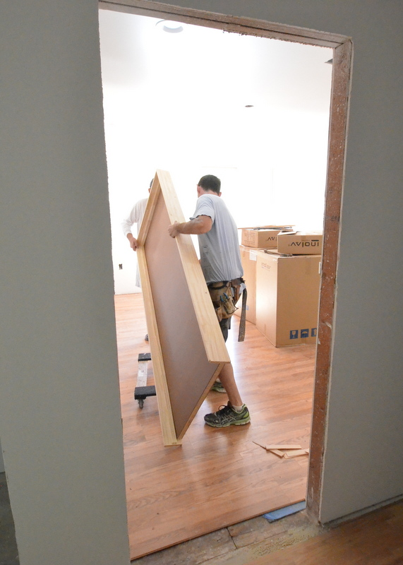 At the back, Patrick tips up and Shane pivots to vertical the door to bedroom 4 from the upstairs hallway.