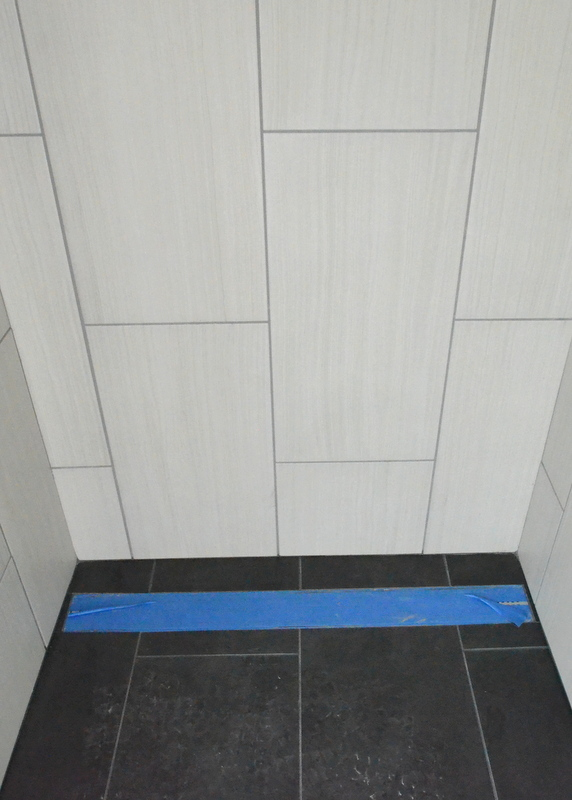 Here's the opposite wall where it meets the floor, near the linear drain, with the grout lines offset from each other.