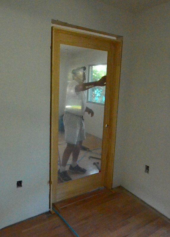 Patrick tests the door to Steven's office for plumb -- and the reveal between the door and the doorjamb.