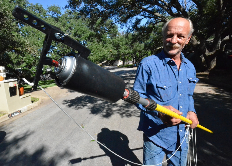 Each of the large cuts to the oaks leaves a wound that must be sealed. Barry shows off the spray can fitted into a sleeve on a long pole, with pull cord -- an assembly used to reach high into the trees to the wounds.