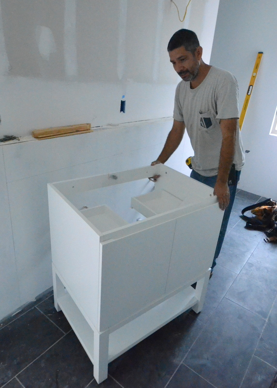 Here is one of the six vanity cabinets that we are using in all the bathrooms. This is the first time the cabinet has been unboxed. Cris as going to install them all today, but ... now the plumbers have to fix the installs. The cabinet, by the way, is beautiful and brilliant, chosen well.