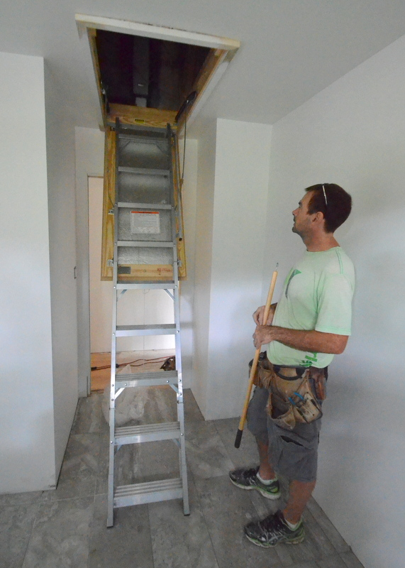 Shane shows the attic stair open and extended. Steven took his first climb. The aluminum is lighter and easier to work with than a heavy wooden attic stair. The unit is also lightly insulated, to help seal off the attic when the ladder is closed against the ceiling.