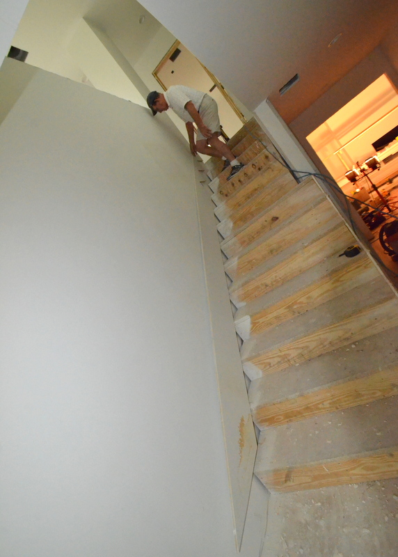 Patrick installs the skirt board along the stairs.