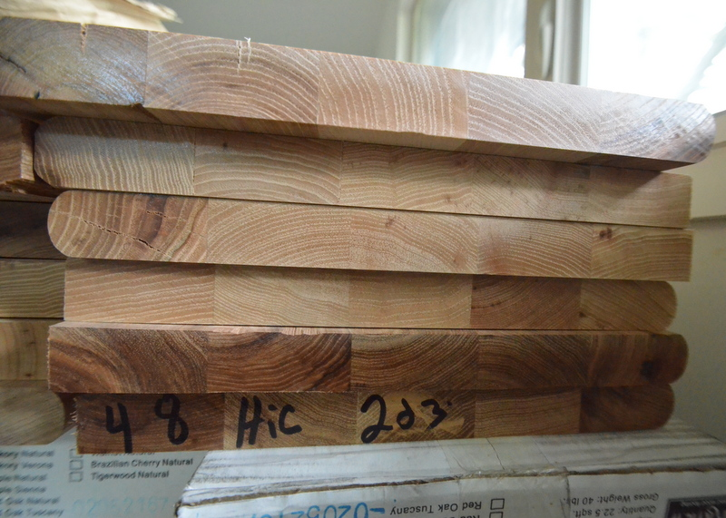 "A stack of treads. Each board is an assembly of narrow planks, glued and clamped together.  These are ""bullnose"" treads. We plan to slice off the rounded edge to get to a squared, modern face."