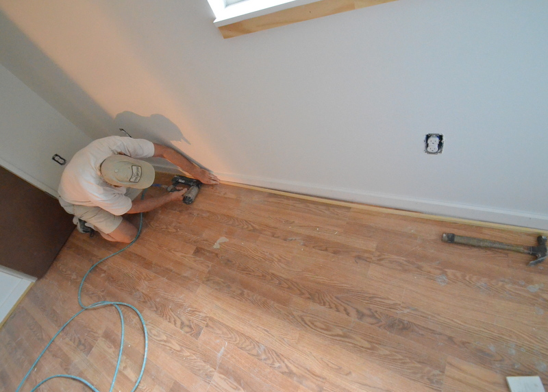 "Peter on his hands and knees nailing the shoe molding to the baseboard above the laminate flooring in bedroom 4. Knee pads might help, but Peter refuses -- ""they make my knees sweat."""